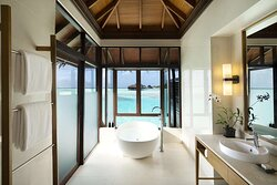 Interior view of bathroom in Deluxe Over Water Bungalow with freestanding bathtub and lagoon view