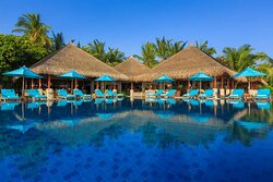 Exterior view of swimming pool at Dhoni Poolside Bar with sun-loungers
