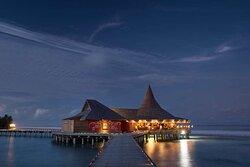 Exterior view of Baan Huraa Thai Restaurant at night with ocean view