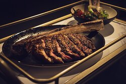 38oz Tomahawk (for 2).. Bone Marrow, Heirloom Tomato, Charred Lime  Our tomahawk is aged for about a week and gets cooked over almond wood.  The bone marrow salsa is made with shallots, Serrano, tomato, green onions, and the bone marrow that gets introduced table side.