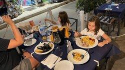 1 soute di cozze  1 antipasto di mare (gamberi calamari cozze polipo seppia verdure e ben condite)  1 piatto di sagne (qui è la pasta della domenica) allo scoglio  1 fritto misto di mare  ( gamberi calamari totani sarde e paranza) 1 piatto di orecchiette al pomodoro fresco (ottime) per bimba 1 salsiccia e patatine fritte per bimba  Vino locale  bianco fermo leggero piacevole  Porzioni abbondanti, il cameriere Stefano,  bravissimo professionale cordiale competente gentile ed educato.
