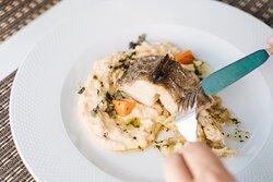 Bacalhau confitado em azeite de alecrim e alho, com cremoso de chicharo, couve branca salteada e cenouras glaceadas