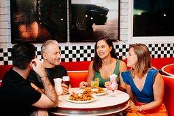 Grupo de amigos em nossa hamburgueria e restaurante do Movie Cars. Porções e Milkshakes e muitas variedades com um visual único dos anos 50.