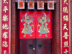 Door gods guard the entrance to a traditional temple on Tai Ping Shan Street.