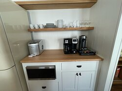 Unit 16 kitchen appliances: Nespresso maker, Keurig / coffee pot, icemaker, cups, glasses and dinnerware.