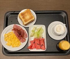 Breakfast of scrambled eggs, bacon, toast, fruit, cappuccino, and freshly squeezed orange juice