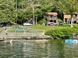 View of swimming area with raft, sandy beach area wtih chairs and guests' chairs in the lawn.  Beautiful locations from which to enjoy gorgeous views of the lake and mountains