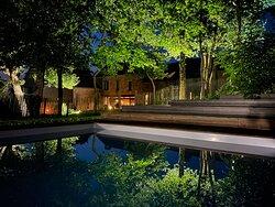 Vue de nuit de la piscine sur la maison