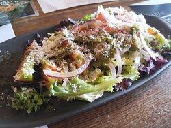 Ensalada de tomate con pesto de albahaca, mezclum, parmesano y cebolla