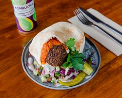 Harissa Pita Falafel, hummus, our famous house-made spicy harissa, tomato and cucumber Israeli salad, pickled cabbage, sumac pickled onion, topped with pickles and tahini.