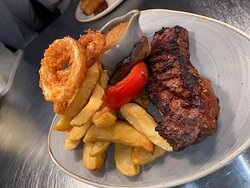 8OZ Sirloin steak served with hand cut chips, battered onion rings and a homemade blue cheese sauce.
