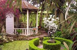 Open tuinhuisje bij ronde vijver.