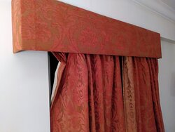 The curtain hanging off of the rail.