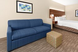 """Relax and unwind in our suites with a king bed, sofa, and 48"""" TV."""