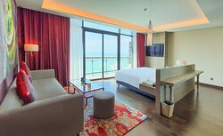 Deluxe Room (Type A) with sea view, balcony and spacious living space area.