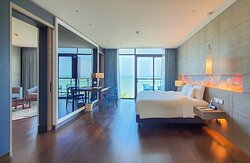 Angsana One-Bedroom Deluxe Suite with balcony, sea view and separate spacious living room area with a cook top.