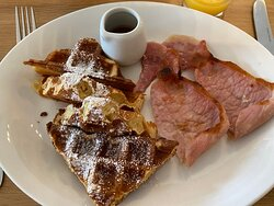 Breakfast of waffles, bacon & maple syrup