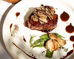 Filet de bœuf, jus de viande, ail confit, copeaux de truffe.
