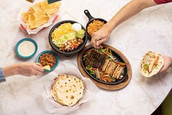 Combo fajitas - marinated in a signature blend of Shiner Bock beer, serrano peppers, lime juice, spices, served with rice, beans, tortillas and all the fixings.