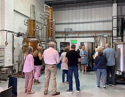A group of visitors stand gathered around Anno's cooper-pot still during a distillery tour.