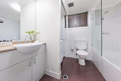 Interior view of bathroom in One Bedroom Suite with shower in bathtub