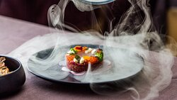 Organic beef tartare with egg yolk confit, trout caviar. Lightly smoked and served under a dome.