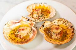 """""""SCALLOPS"""" Freshly baked scallops served in a shell with garlic butter and Bacon."""