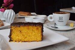 Café com bolo de cenoura com cobertura de chocolate.