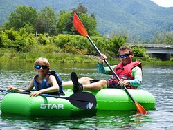 A super way to keep connected, putting your feet on the tube in front is a safe way to float together.  Guided River Tubing Watauga River