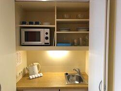 Pequeño espacio con nevera, microondas, cubiertos y vajilla.