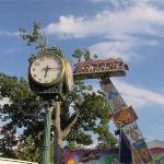 "Classic park clock with Ali Baba ""Magic Carpet"" Ride in the foreground"