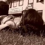 my friend sunbathes on the grass in front of the hostel