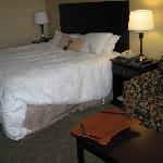 Dreamy bed and linens; note reading stand on coffee table
