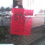 Building violation sign, left on lobby window