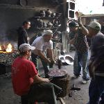 Workers forging copper. Several of the shop in town have workshops out back.