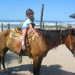 daughter riding horse on beach
