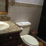 Bathroom with granite countertop, toiletries, water bottles, plush towels, hair dryer
