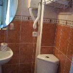 Salle de douches avec lavabo et WC en coin.