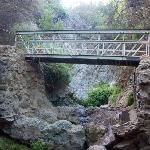 Bridge crossing over creek, between two non-flowing waterfalls