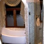 the slipper tub and separate tiled shower of the Zebra Suite