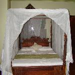 Bed with large stained glass window behind