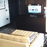 The settee at the end of the bed with flat screen TV in the suite