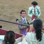 The best of the bullfighters carrying flowers and the ear of his bull.