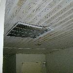 outside room, dented, rusty ceiling, AC duct held up with zip ties.