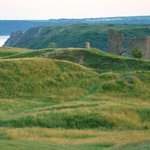 view from 7th tee Pennard Golf Course of castle & 3 cliffs in background