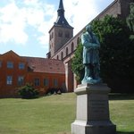 Church in Odense, Denmark with a statue of Hans Christian Andersen.