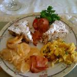 Beautiful arrangment of scrambled eggs, potatoes, bacon and banana and bluberry cakes