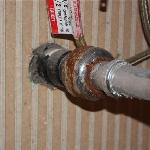 Plumbing under the sink which is dusty and rusty in full view when sitting on the toilet