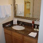 The sink area of the bathroom with the rooms only Mirror.