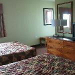 Two comfortable beds, dresser, closet, balcony entrance.